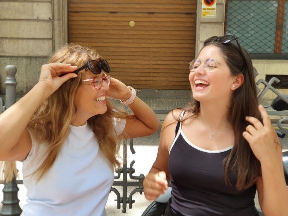 Anna und ihre Tochter Sofia lachen aus vollem Herzen. Sie tragen jeweils eine optische BRille und eine Sonnenbrille auf der Stirn.
