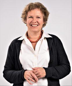 Ina Rodewald trägt eine weißer Bluse und einen schwarzem Kardigan und lächelt freundlich.